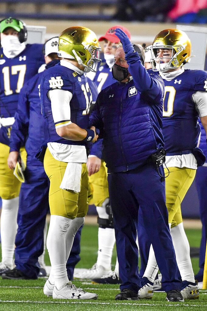 Notre Dame quarterback Ian Book (12) is greeted by coach Brian Kelly after coming out of the game during the fourth quarter of the team's NCAA college football game against Syracuse on Saturday, Dec. 5, 2020, in South Bend, Ind. (Matt Cashore/Pool Photo via AP)