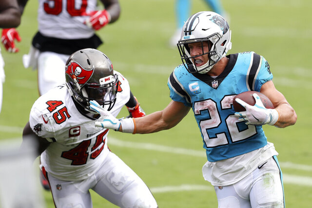 Carolina Panthers running back Christian McCaffrey (22) stiff arms Tampa Bay Buccaneers linebacker Devin White (45) as he scores on a touchdown run during the second half of an NFL football game Sunday, Sept. 20, 2020, in Tampa, Fla. (AP Photo/Mark LoMoglio)