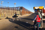 In this Jan. 10, 2020, photo, a snack vendor stands on a street as a cyclist goes by in San Luis Rio Colorado, Mexico, leading to a border crossing in San Luis, Ariz. Months earlier, asylum seekers waited in line in tents in San Luis Rio Colorado, Mexico. Illegal border crossings have plummeted as the Trump administration extended a policy to make asylum seekers wait in Mexico for court hearings in the U.S. (AP Photo/Elliot Spagat)