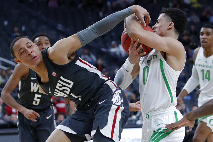 Washington State's Jervae Robinson, left, tries to take the ball from Oregon's Will Richardson during the second half of an NCAA college basketball game in the first round of the Pac-12 men's tournament Wednesday, March 13, 2019, in Las Vegas. (AP Photo/John Locher)
