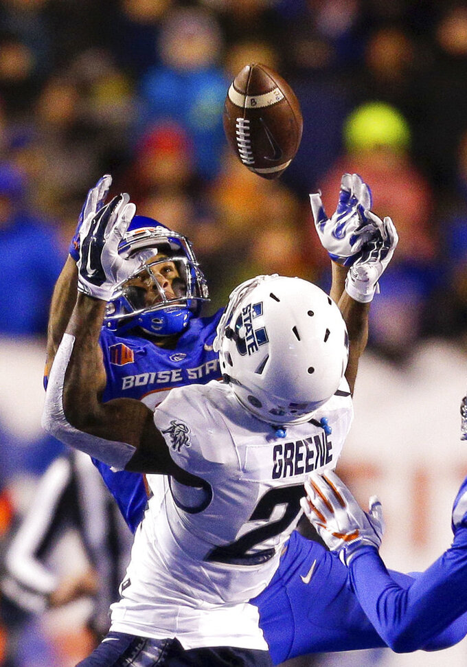 Boise State cornerback Avery Williams, left, battles with Utah State wide receiver Jalen Greene (21) for the ball on a pass in the second of an NCAA college football game, Saturday, Nov. 24, 2018, in Boise, Idaho. Boise State won 33-24. (AP Photo/Steve Conner)