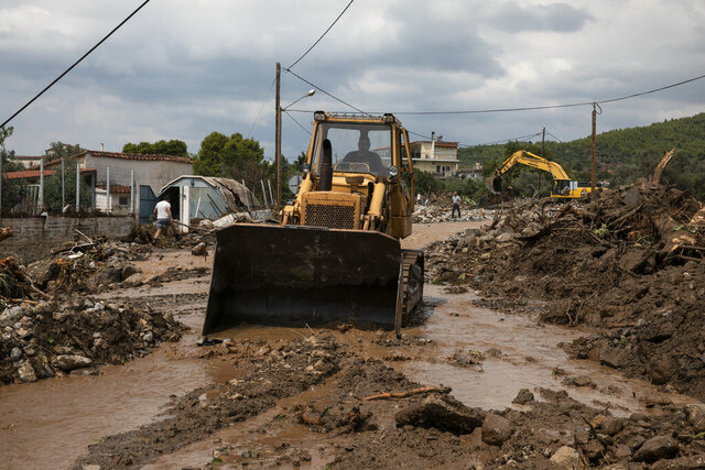 Heavy machinery moves away debris from a destroyed street following a storm at the village of Politika, on Evia island, northeast of Athens, on Sunday, Aug. 9, 2020. An elderly couple and an 8-month-old baby have been found dead and dozens have been trapped in their homes and cars from a storm that has hit the island of Evia, in central Greece, police say. (AP Photo/Yorgos Karahalis)