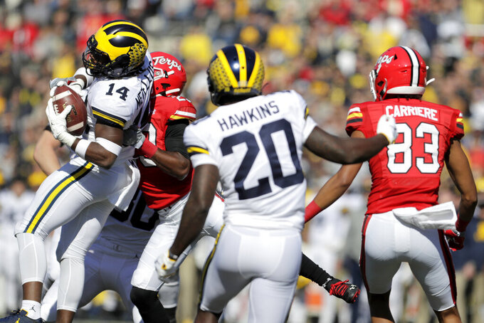 Michigan defensive back Josh Metellus (14) intercepts a pass from Maryland quarterback Josh Jackson, as Maryland's Sean Savoy tries to bring him down during the first half of an NCAA college football game, Saturday, Nov. 2, 2019, in College Park, Md. (AP Photo/Julio Cortez)