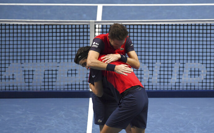 Pierre-Hugues Herbert of France, front left, and Nicholas Mahut of France celebrate after defeating Raven Klaasen of South Africa and Michael Venus of New Zealand following their ATP World Finals final doubles tennis match at the O2 arena in London, Sunday, Nov. 17, 2019. (AP Photo/Alberto Pezzali)
