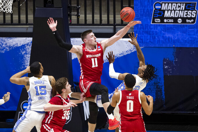 Wisconsin's Micah Potter (11) blocks a shot by North Carolina's Caleb Love (2) during the first half of a first-round game in the NCAA men's college basketball tournament Friday, March 19, 2021, at Mackey Arena in West Lafayette, Ind. (AP Photo/Robert Franklin)