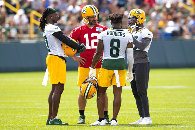 FILE - Green Bay Packers' Davante Adams, left, Aaron Rodgers (12), Amari Rodgers (8) and Randall Cobb talk during an NFL football training camp practice at Ray Nitschke Field in Green Bay, Wisc., in this Monday, Aug. 2, 2021, file photo. Cobb, who previously played for the Packers from 2011-18, returned to Green Bay at the start of training camp in a trade that sent an undisclosed draft pick to the Houston Texans. (Samantha Madar/The Post-Crescent via AP, File)/