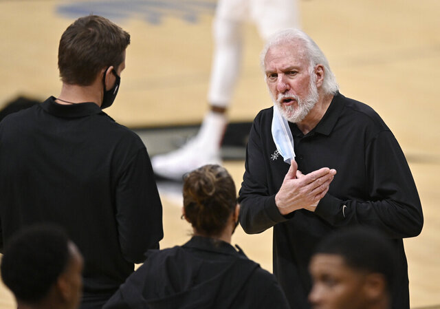 San Antonio Spurs coach Gregg Popovich, right, talks to assistant coaches Becky Hammon, center, and Will Hardy during the second half of the team's NBA basketball game against the Toronto Raptors, Saturday, Dec. 26, 2020, in San Antonio. San Antonio won 119-114. (AP Photo/Darren Abate)