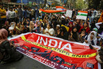 Indians block a road as they participate in a rally to protest against a new citizenship law, in Kolkata, India, Tuesday, Jan. 21, 2020. India has been embroiled in protests since December, when Parliament passed a bill amending the country's citizenship law. The new law provides a fast track to naturalization for some migrants who entered the country illegally while fleeing religious persecution. But it excludes Muslims, which critics say is discriminatory and a violation of India's Constitution. (AP Photo/Bikas Das)