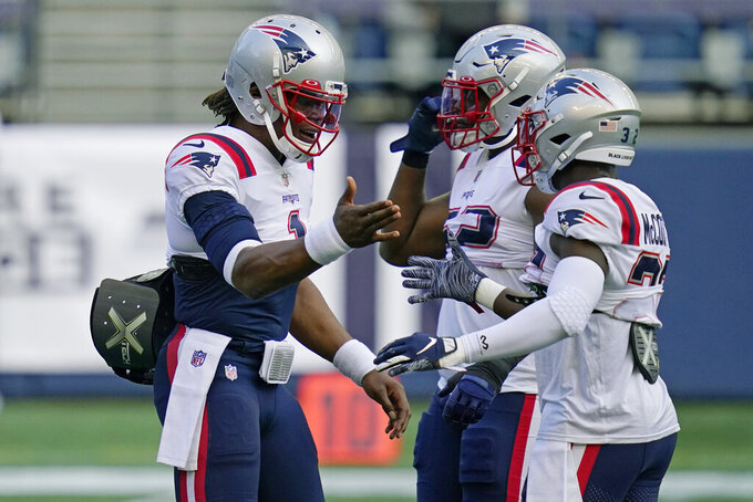 New England Patriots quarterback Cam Newton, left, greets cornerback Jason McCourty, right, during warmups before an NFL football game against the Seattle Seahawks, Sunday, Sept. 20, 2020, in Seattle. (AP Photo/Elaine Thompson)