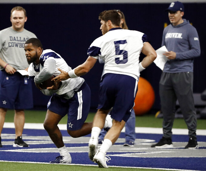 In this Friday, May 10, 2019 photo, Dallas Cowboys rookie running back Mike Weber Jr., left, takes a hand off from rookie quarterback Phillip Nelson (5) during a NFL football mini camp at the team's training facility in Frisco, Texas. (AP Photo/Tony Gutierrez)