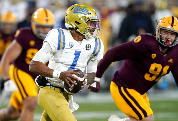 FILE - In this Dec. 5, 2020, file photo, UCLA quarterback Dorian Thompson-Robinson (1) scrambles during the first half of an NCAA college football game, in Tempe, Ariz. Thompson-Robinson has gone on to start 24 of the 26 games he has played. Last season he completed a career high 65.2% of his passes with 12 touchdowns and four interceptions. (AP Photo/Matt York,File)