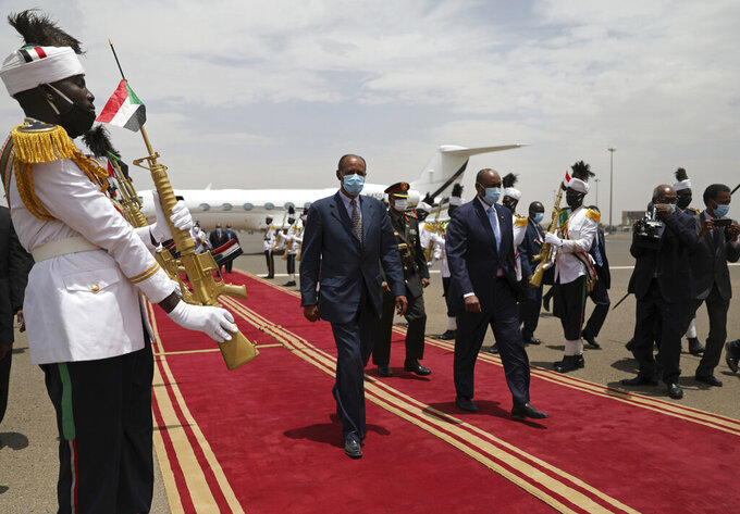 President of the Sudanese Transitional Council General Abdel Fattah al-Burhan, center right, walks on the red carpet with Eritrean President Isaias Afwerki at the Khartoum airport, in Khartoum, Sudan, Tuesday, May 4, 2021. Eritrea's president arrived in Khartoum on Tuesday for talks with Sudanese officials amid tensions between the two countries over the Tigray conflict on Sudan's border. (AP Photo/Marwan Ali)