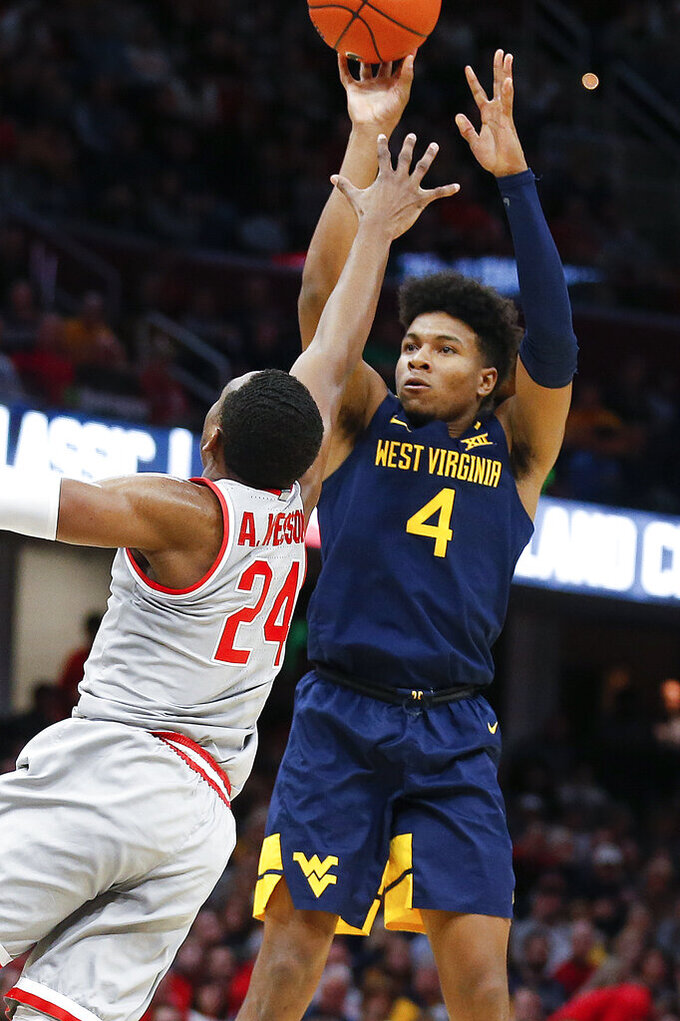 West Virginia's Miles McBride (4) shoots over Ohio State's Andre Wesson (24) during the second half of an NCAA college basketball game Sunday, Dec. 29, 2019, in Cleveland. West Virginia defeated Ohio State 67-59. (AP Photo/Ron Schwane)