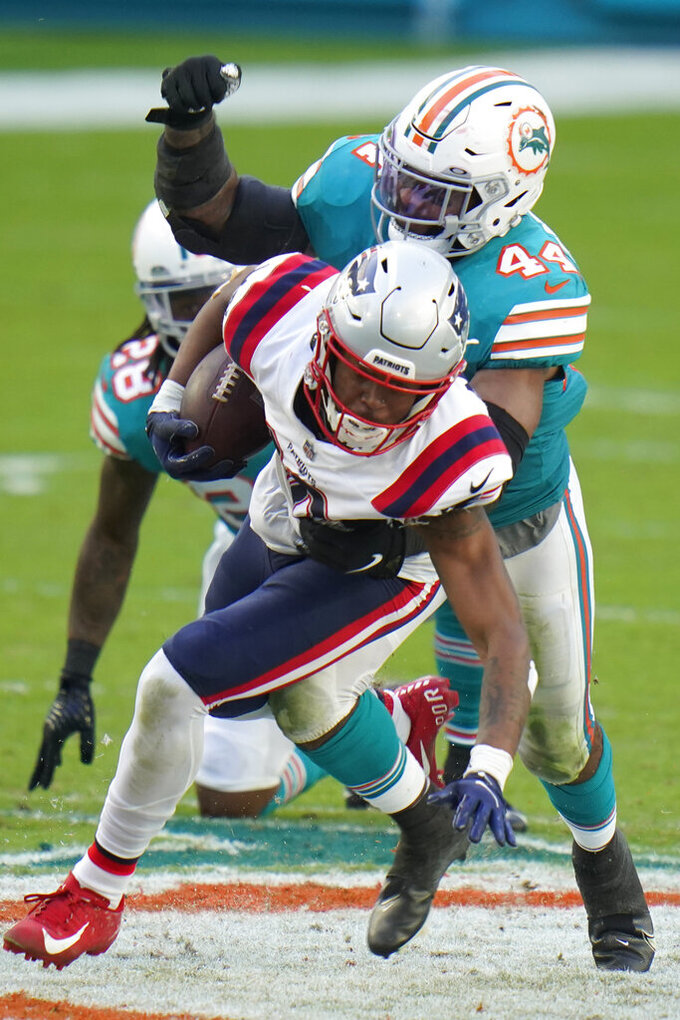 Miami Dolphins outside linebacker Elandon Roberts (44) tackles New England Patriots wide receiver Jakobi Meyers (16), during the second half of an NFL football game, Sunday, Dec. 20, 2020, in Miami Gardens, Fla. (AP Photo/Chris O'Meara)