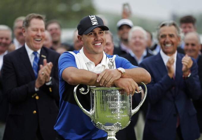 FILE - In this May 19, 2019, file photo, Brooks Koepka poses with the Wanamaker Trophy after winning the PGA Championship golf tournament at Bethpage Black in Farmingdale, N.Y. Brooks Koepka will try to become the first player to win the PGA Championship three straight times in stroke play, and there won't be anyone at Harding Park to cheer him on. The PGA of America confirmed Monday, June 22, 2020, the first major of this most unusual year won't have spectators.(AP Photo/Julio Cortez, FIle)