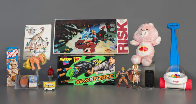 In this Aug. 13, 2019 photo provided by the National Toy Hall of Fame are the 2019 finalists, from left to right, Jenga, Magic the Gathering, My Little Pony, Coloring Book, Matchbox Cars, Top, Nerf Blaster, Risk, Masters of the Universe, Care Bears, Smartphone, and Fisher-Price Corn Popper. The smartphone is being considered for induction into the National Toy Hall of Fame this year in recognition of the way it has changed how people of all ages play and interact. (National Toy Hall of Fame via AP)