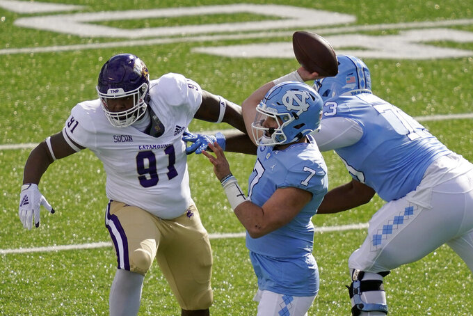 North Carolina quarterback Sam Howell (7) passes while Western Carolina defensive tackle Jaquarius Guinn (91) rushes during the first half of an NCAA college football game in Chapel Hill, N.C., Saturday, Dec. 5, 2020. (AP Photo/Gerry Broome)