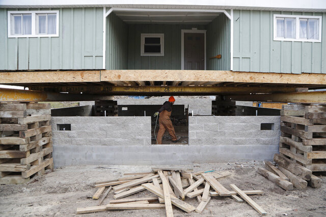 In this Wednesday, Jan. 8, 2020, file photo, laborer Logan Farrington works under a house being lifted in Luna Pier, Mich. The project will protect the home from the potential rising lake levels of Lake Erie. High water is wreaking havoc across the Great Lakes, which are bursting at the seams less than a decade after bottoming out. The sharp turnabout is fueled by the region's wettest period in more than a century that scientists say is likely connected to the warming climate. Road damage from the overflowing Great Lakes and inland waterways may carry a whopping price tag for Michigan. Brad Wieferich of the state Department of Transportation said Monday Feb. 10, 2020, about 40 locations have been hit especially hard. He says initial estimates suggest about $5 million will be needed for immediate fixes. (AP Photo/Carlos Osorio File)