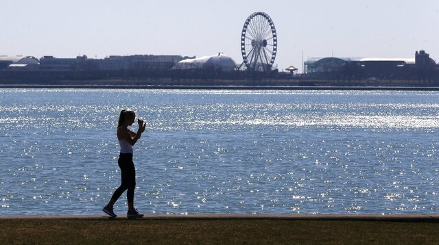 FILE - In this March 24, 2017 file photo, a lone woman walks the trail along Lake Michigan at Chicago' North Avenue beach. Additional funds provided by Congress for Great Lakes environmental improvements will be used to quicken cleanups of highly toxic sites and step up work on other longstanding forms of pollution, federal officials said Thursday, April, 9, 2020. (AP Photo/Charles Rex Arbogast, File)