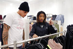 Houston Texans player Kenny Stills helps Miracle Washington-Tribble pick out clothes at H&M on Monday, Dec. 16, 2019, at Galleria Mall in Houston. Washington-Tribble is one of two teens at the event who are beneficiaries of Eight Million Stories, a Houston program which helps 14-18-year-olds who have either quit or been kicked out of school continue their education, find employment and receive emotional support. (AP Photo/Michael Wyke)