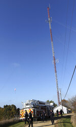 A base jumper was rescued from a city of Menomonie bucket truck after he became tangled in guy wires of a 300 ft. tower he jumped from in Menomonie, Wis., on Thursday, Oct. 17, 2019. He was arrested for criminal trespass after his parachute got tangled in the guy wires of a cell phone tower in northwestern Wisconsin. Police say the 20-year-old man was illegally jumping from a 300-foot Charter Communications tower in Menomonie Thursday when his chute got tangled in the wires leaving him dangling 50 feet above ground. He called police for help.(Dan Reiland/The Eau Claire Leader-Telegram via AP)