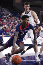 Detroit Mercy guard Antoine Davis, left, drives the ball around Gonzaga forward Filip Petrusev during the first half of an NCAA college basketball game in Spokane, Wash., Monday, Dec. 30, 2019. (AP Photo/Young Kwak)