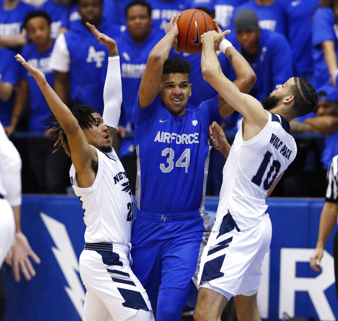 Air Force forward Ryan Swan, center, looks to pass the ball under pressure from Nevada guard Jazz Johnson, left, and forward Caleb Martin during the first half of an NCAA college basketball game Tuesday, March 5, 2019, at Air Force Academy, Colo.(AP Photo/David Zalubowski)