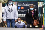 People wearing protective masks during the coronavirus pandemic exit the Kew Gardens subway station Monday, Oct. 5, 2020, in the Kew Gardens neighborhood of the Queens borough of New York. New York Gov. Andrew Cuomo on Monday ordered schools in certain New York City neighborhoods closed within a day in an attempt to halt flare-ups of the coronavirus. (AP Photo/Frank Franklin II)