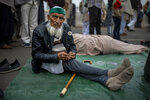 87-year old farmer Mohammad Abid listens to a speaker along with fellow farmers as they block a major highway in a protest against new farm laws at the Delhi-Uttar Pradesh state border, India, Friday, Jan. 8, 2021. (AP Photo/Altaf Qadri)