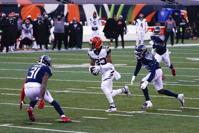 Cincinnati Bengals' Tyler Boyd (83) runs against Tennessee Titans' Kevin Byard (31) and Chris Jackson (35) during the second half of an NFL football game, Sunday, Nov. 1, 2020, in Cincinnati. (AP Photo/Bryan Woolston)