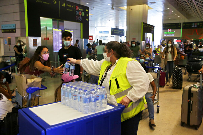 An airport worker hands out water bottles to passengers queueing at Lisbon airport, Saturday, July 17, 2021. A strike by ground handling workers at Portugal's airports forced the cancellation of over 200 flights on Saturday. The walkouts over wage conditions are scheduled to last through Sunday. (AP Photo/Armando Franca)