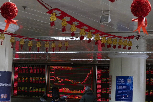 Investors monitor stock prices near Chinese New Year decorations hung up at a brokerage in Beijing Thursday, Jan. 16, 2020. Share prices are mixed in moderate trading in Asia after the U.S. and China signed a preliminary trade agreement that investors hope will bring better relations between the two biggest economies. (AP Photo/Ng Han Guan)