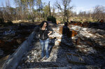In this Friday, Oct. 18, 2019, photo, Amber Blood looks over the burned remains of the home she lost in last year's Camp Fire in Paradise, Calif. Blood is one of the estimated 20,000 former Paradise residents now living in Chico after the fire. A real estate agent, Blood said even she had trouble finding a home after the fire because there was not much available. (AP Photo/Rich Pedroncelli)