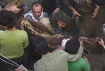 In this frame grab from from video, people carry a child's body after pulling it out from rubble following Saudi-led coalition airstrikes that killed at least six, including four children, officials said, in the residential center of the capital, Sanaa, Yemen, Thursday, May 16, 2019. The Sanaa airstrikes came after Yemen's Iran-backed Houthi rebels, who control the capital, launched a drone attack earlier in the week on a critical oil pipeline in Saudi Arabia, Tehran's biggest rival in the region. (AP Photo)