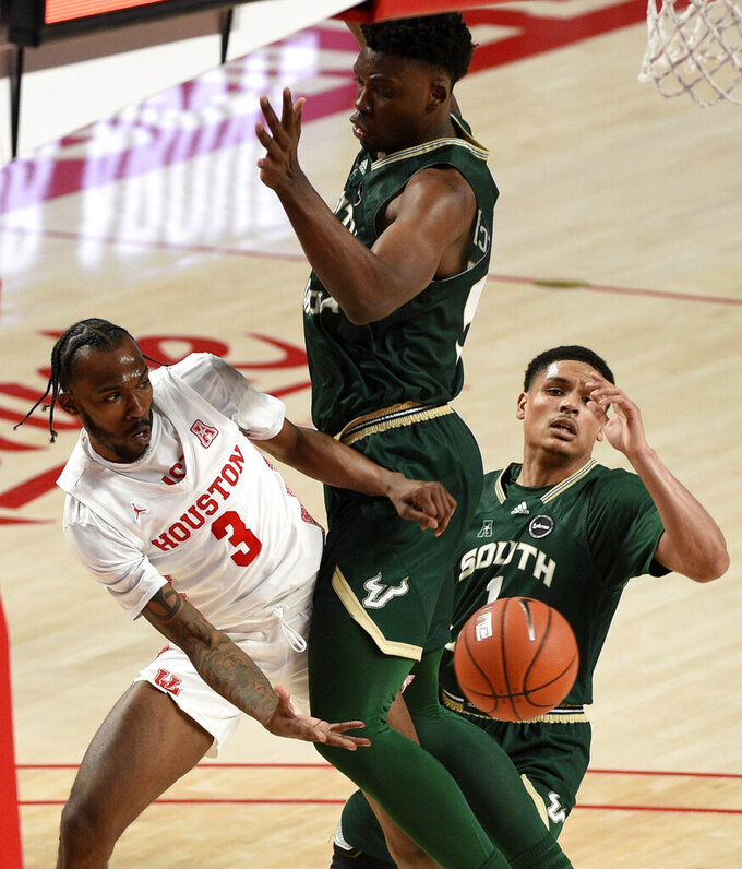 Houston guard DeJon Jarreau (3) passes the ball around South Florida center Russel Tchewa, center, during the second half of an NCAA college basketball game, Sunday, Feb. 28, 2021, in Houston. (AP Photo/Eric Christian Smith)