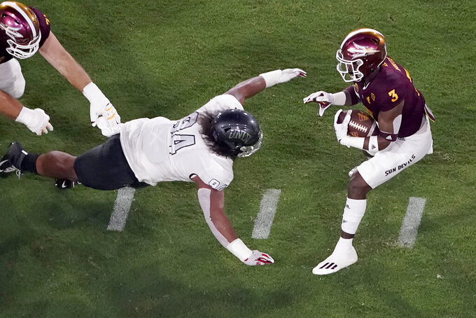 UNLV defensive lineman Kolo Uasike lunges for Arizona State running back Rachaad White (3) during the first half of an NCAA college football game, Saturday, Sept. 11, 2021, in Tempe, Ariz. (AP Photo/Matt York)