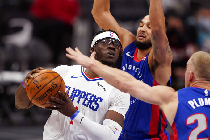 LA Clippers guard Reggie Jackson drives as Detroit Pistons center Mason Plumlee (24) and guard Cory Joseph defend during the first half of an NBA basketball game, Wednesday, April 14, 2021, in Detroit. (AP Photo/Carlos Osorio)
