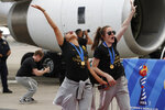 Two members of the United States women's soccer team, winners of a fourth Women's World Cup, celebrate after arriving at Newark Liberty International Airport, Monday, July 8, 2019, in Newark, N.J. (AP Photo/Kathy Willens)
