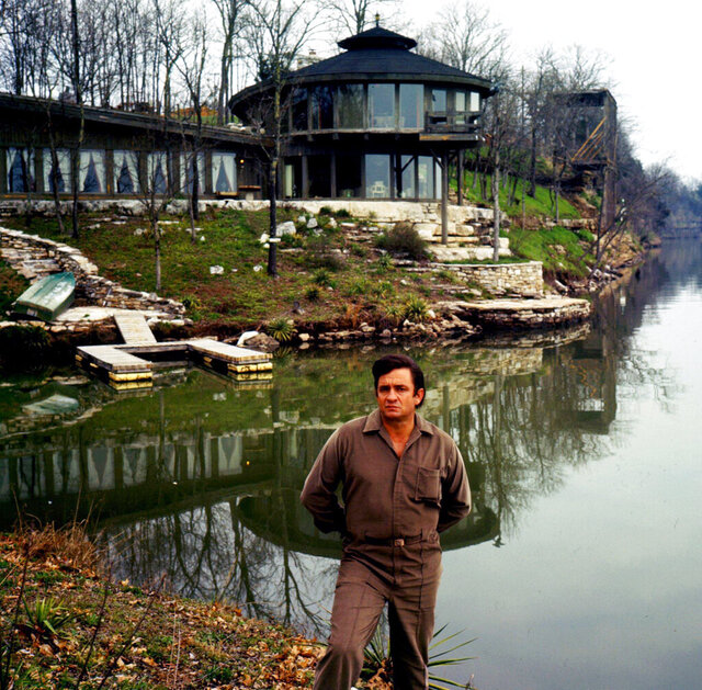 FILE - This April 19, 1969 file photo shows country legend Johnny Cash posing by his home on Old Hickory Lake near Hendersonville, Tenn.  The lake house belonging to the couple burned down in 2007.  The Hendersonville Standard reported a local couple bought the 4.5-acre property in Hendersonville in January.  (J.T. Phillips/The Tennessean via AP)
