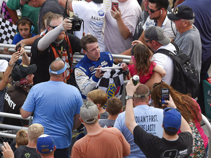AJ Allmendinger, center, celebrates with fans in the stands and gives a young girl the checkered flag after winning a NASCAR Xfinity Series auto race at Charlotte Motor Speedway, Saturday, Sept. 28, 2019, in Concord, N.C. (AP Photo/Mike McCarn)