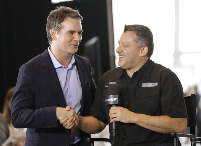 Tony Stewart, right, is congratulated by Jeff Gordon after being named to the NASCAR Hall of Fame class of 2020 during an announcement in Charlotte, N.C., Wednesday, May 22, 2019. (AP Photo/Chuck Burton)