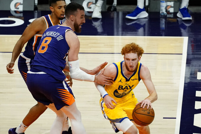 Golden State Warriors guard Nico Mannion (2) drives past Phoenix Suns forward Frank Kaminsky (8) during the first half of an NBA basketball game, Thursday, March 4, 2021, in Phoenix. (AP Photo/Rick Scuteri)