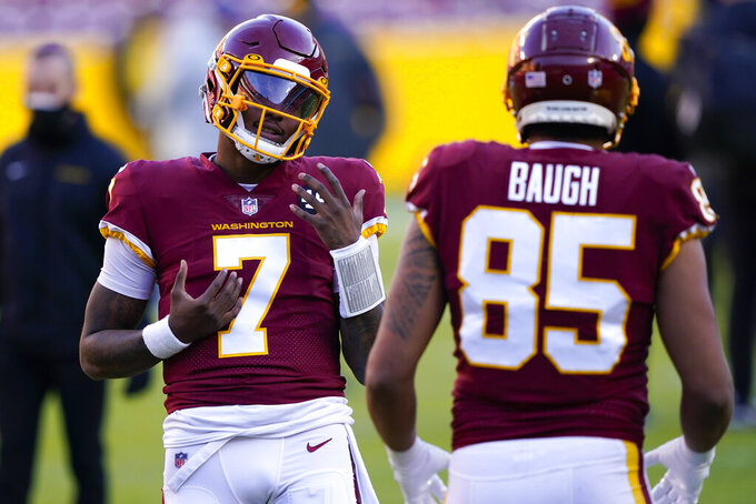 Washington Football Team quarterback Dwayne Haskins (7) talks with teammate tight end Marcus Baugh (85) before the start of an NFL football game against the Carolina Panthers, Sunday, Dec. 27, 2020, in Landover, Md. (AP Photo/Susan Walsh)
