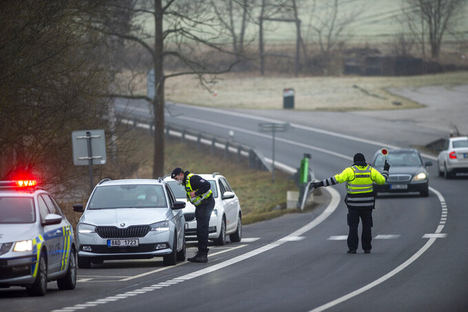 Police officers check cars on a road between the towns, Ceske Budejovice and Cesky Krumlov, near Kosov, Czech Republic, Monday, March 1, 2021. Limits for free movement of people are set in place in the Czech Republic. Travelling to other counties unless they go to work or have to take care about relatives is prohibited.(Vaclav Pancer/CTK via AP)