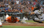San Francisco Giants' Brandon Crawford slides into home plate to score the Giants' third run as Pittsburgh Pirates catcher Francisco Cervelli reaches in vain for him during the first inning of a baseball game Friday, Aug. 10, 2018, in San Francisco. (AP Photo/Eric Risberg)
