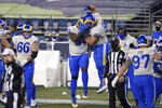 Los Angeles Rams A'Shawn Robinson (94) and Greg Gaines (91) leap in celebration after they defeated the Seattle Seahawks in an NFL wild-card playoff football game, Saturday, Jan. 9, 2021, in Seattle. (AP Photo/Ted S. Warren)