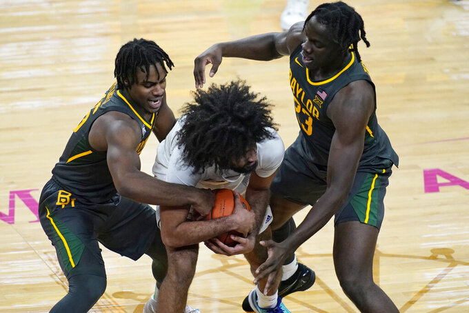 Baylor's Davion Mitchell, left, and Jonathan Tchamwa Tchatchoua, right, guard Washington's Marcus Tsohonis during the second half of an NCAA college basketball game Sunday, Nov. 29, 2020, in Las Vegas. (AP Photo/John Locher)