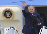 FILE - In this Aug. 15, 2008, file photo, President George W. Bush, carrying his dog Barney, waves as he arrives at TSTC airfield in Waco, Texas, to begin his summer vacation at his ranch near Crawford Texas. President Donald Trump isn't hiding the fact that he isn't a dog person. While he appeared impressed when describing the drug-detecting abilities of German shepherds that work for the U.S. Secret Service, he made it clear that he can get by in his daily life without the slobbery canine companionship welcomed by many of his predecessors.(AP Photo/Rod Aydelotte, File)