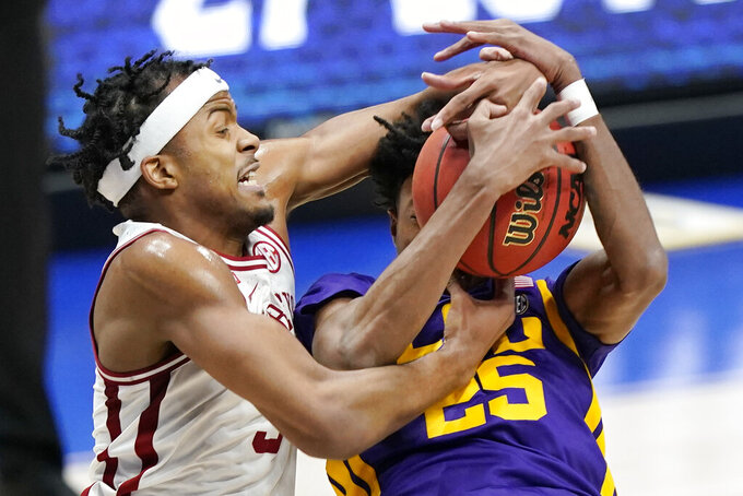 Arkansas' Moses Moody, left, and LSU's Eric Gaines (25) fight for a rebound in the first half of an NCAA college basketball game in the Southeastern Conference Tournament Saturday, March 13, 2021, in Nashville, Tenn. (AP Photo/Mark Humphrey)
