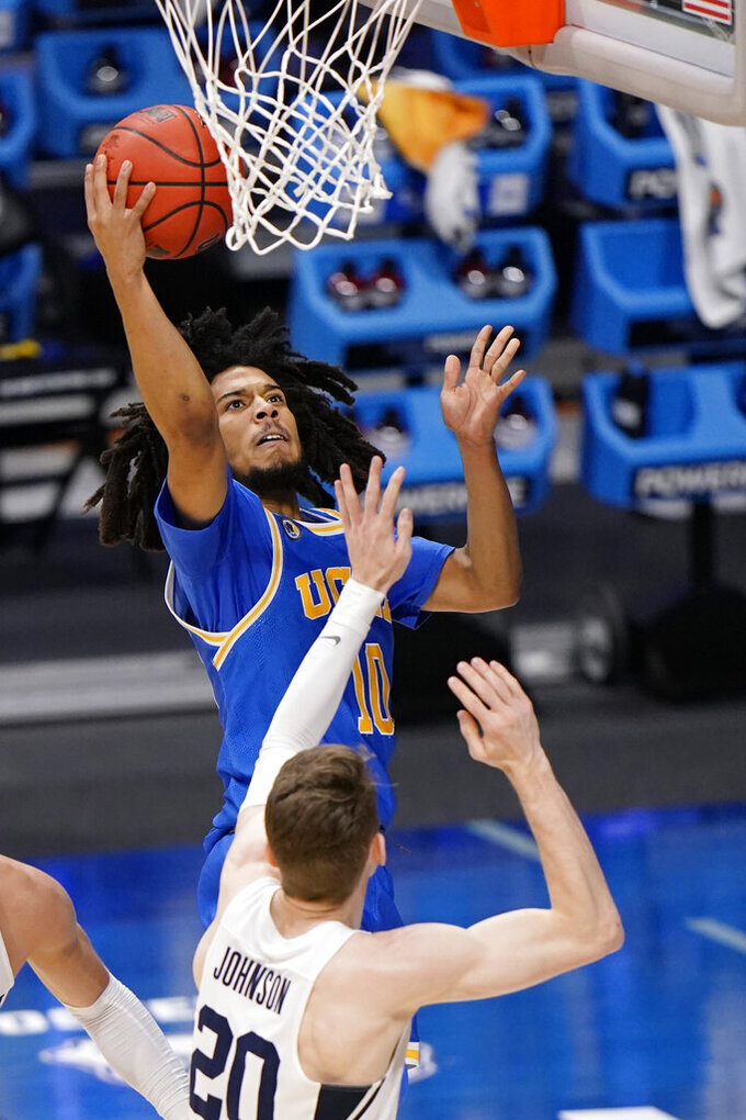 UCLA guard Tyger Campbell (10) takes a shot over BYU guard Spencer Johnson (20) during the second half of a first-round game in the NCAA college basketball tournament at Hinkle Fieldhouse in Indianapolis, Saturday, March 20, 2021. (AP Photo/AJ Mast)